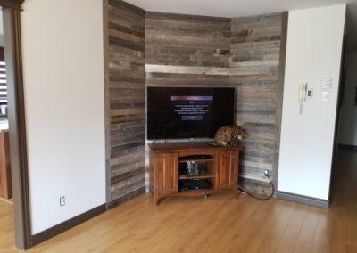Mur de salon en bois de grange gris avec meuble de télé