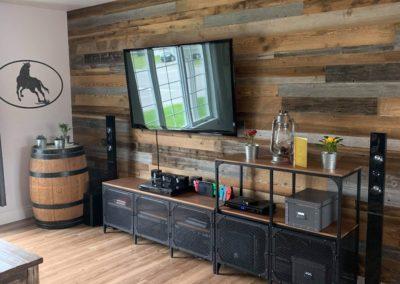 Mur de salon en bois de grange brun et gris avec meubles en acier